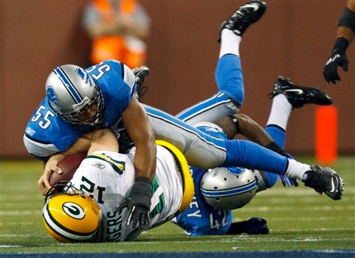 Green Bay Packers quarterback Aaron Rodgers (12) gets tackled by Detroit Lions linebacker Landon Johnson (55) and is knocked out of the game in the second quarter of the NFL football game in Detroit, Sunday, Dec. 12, 2010. (AP Photo/Rick Osentoski)