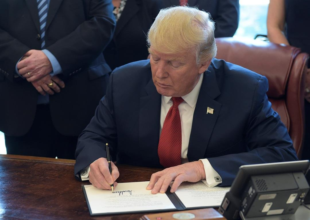 President Donald Trump signs an executive memorandum on investigation of steel imports, Thursday, April 20, 2017, in the Oval Office of the White House in Washington. (AP Photo/Susan Walsh)