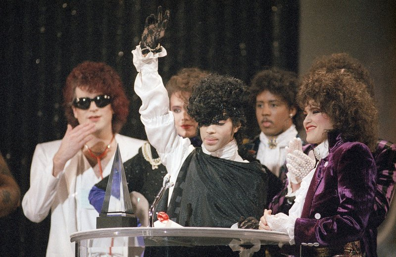 "In this Jan. 28, 1985 file photo, pop vocalist Prince holds up a hand as he and his band The Revolution accept the American Music Award for best single ""When Doves Cry"" in Los Angeles."