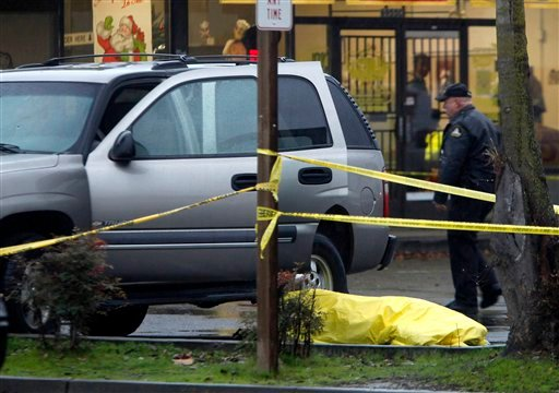 A Sacramento County Sheriff's deputy walks past the tarp covered body of a woman who was shot and killed after being caught in the cross fire between two groups of men in a strip mall in Sacramento, Calif., Tuesday, Dec. 14, 2010.