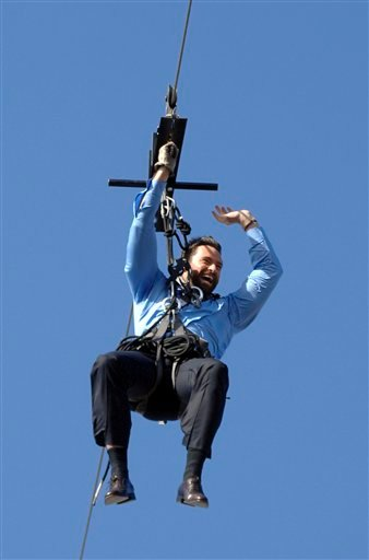 """Australian actor Hugh Jackman makes an aerial entrance on a flying fox (zipline) from the roof of the Opera House during the filming of """"Oprah's Ultimate Australian Adventure""""."""