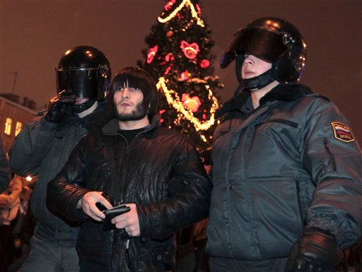 Riot police officers detain protester outside Sennaya Ploshchad metro station in St. Petersburg on Wednesday, Dec. 15, 2010.