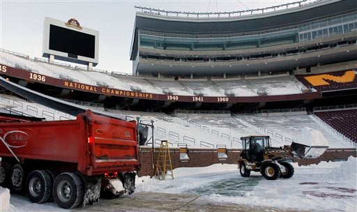 A front-end loader hauls a load of snow to a waiting truck as workers remove snow from the field of TCF Stadium, home of the University of Minnesota football team, Tuesday, Dec. 14, 2010, in Minneapolis.