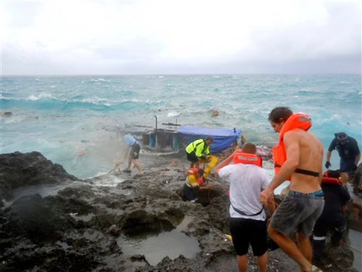People clamber on the rocky shore on Christmas Island during a rescue attempt as a boat breaks up in the background Wednesday, Dec. 15, 2010.