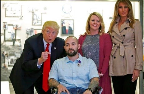 President Donald Trump, left, points after awarding a Purple Heart to U.S. Army Sgt. First Class Alvaro Barrientos.