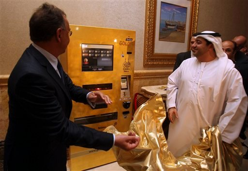 Photo made available by Ex Oriente Lux company: Thomas Geissler the CEO of Ex Oriente Lux, left, and an Emirati official remove the cover of an ATM-style kiosk which monitors the daily gold price and offers small bars. (AP Photo/ Ex Oriente Lux, File)