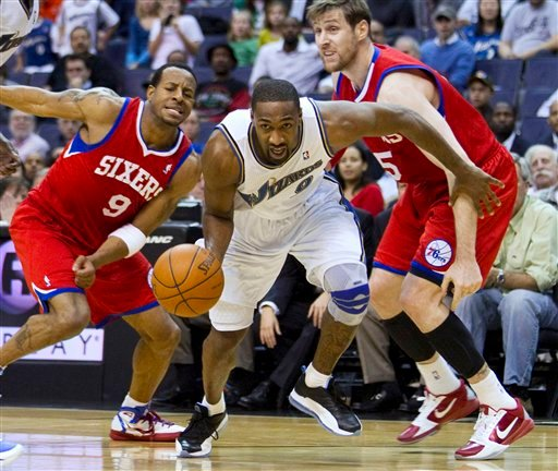 This Nov. 23, 2010, file photo shows Washington Wizards guard Gilbert Arenas, center, driving past Philadelphia 76ers guard Andre Iguodala, left, and forward Andres Nocioni during the second half of an NBA basketball game, in Washington. (AP Photo/Evan Vu