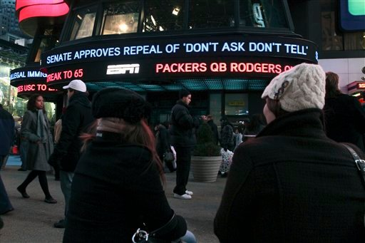 """Cassandra Melnikow, foreground left, and her sister Victoria Melnikow, right, sit in New York's Times Square as news of the Senate approving the repeal of """"Don't Ask Don't Tell"""" is displayed outside ABC Television's Times Square studios. (AP)"""