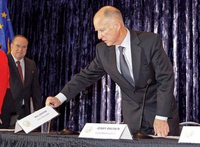 California Gov.-elect Jerry Brown checks the place cards as Treasurer Bill Lockyer, left, joins him for a public panel discussion of the state budget on the campus of UCLA in Los Angeles Tuesday, Dec. 14, 2010.