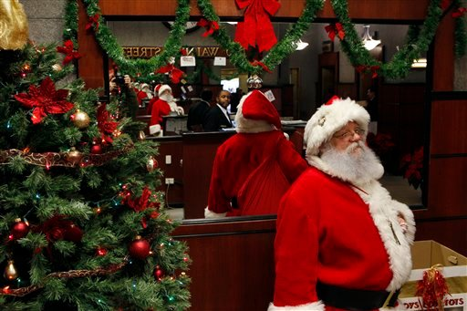 John Wenner is dressed as Santa Claus as he waits to greet people in Friday, Dec. 17, 2010, in Philadelphia, Pa. Bookings for Santas are down this year because of the economy. (AP Photo/Mel Evans)
