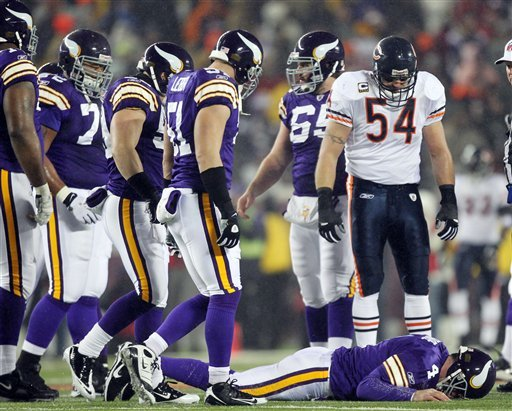 Chicago Bears' Brian Urlacher (54) looks down as Minnesota Vikings quarterback Brett Favre (4) lies on the ground after being hit during the first half an NFL football game Monday, Dec. 20, 2010, in Minneapolis. (AP Photo/Andy King)