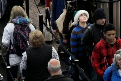While wearing a green Santa hat, Colter Schoer, 10, of Denver, joins the holiday crowd in the long but swiftly moving security line at Denver International Airport, Tuesday, Dec. 21, 2010.