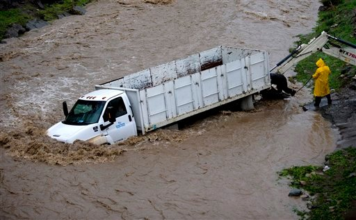 People attempt to pull a truck out of the rain-swollen Santiago Creek near Modjeska Canyon, Calif. on Tuesday, Dec. 21, 2010. (AP Photo/Orange County Register, Mark Rightmire)