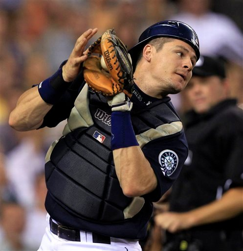 In this July 9, 2010, file photo, Seattle Mariners' Rob Johnson fields the ball during a baseball game against the New York Yankees in Seattle. The Mariners traded Johnson to the San Diego Padres on Tuesday, Dec. 21, 2010, for a player to be named later o