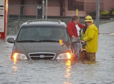 A firefighter helps a woman from her vehicle in a flooded street in Los Angeles Thursday, Dec. 22, 2010.