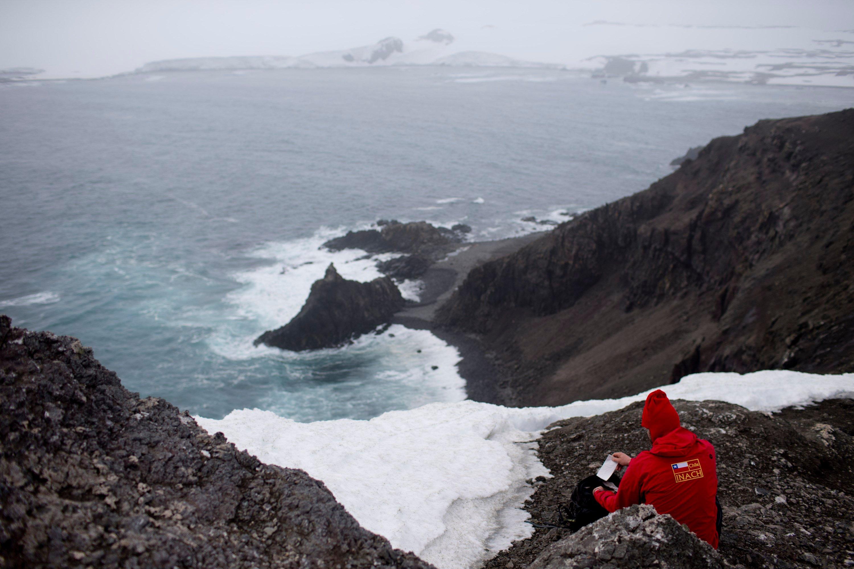 FILE - In this Jan. 24 2015, file photo, German scientist Andreas Beck takes notes in Robert Island, in the South Shetland Islands archipelago, Antarctica. (AP Photo/Natacha Pisarenko, File)