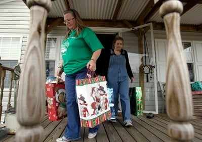 In this Dec. 21, 2010 photo, Vickie Perrin, left, and Joannie Hughes carry Christmas gifts that they plan to distribute to 112 Plaquemines Parish families, many of whom were impacted by the BP PLC oil spill, in Jesuit Bend, La.