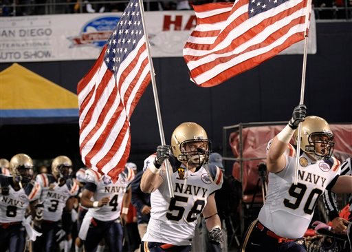 Navy's Billy Yarborough, right, and Trey Grissom carry United States flags as they lead their team onto the field for the Poinsettia Bowl against San Diego State