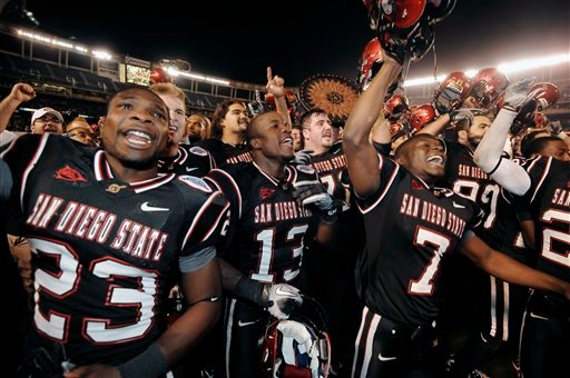San Diego State players Brandon Sullivan, left, Ronnie Hillman, center, and Derek Mack lead the celebration after their 35-14 victory over Navy in the Poinsettia Bowl