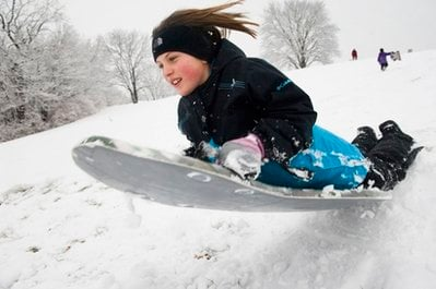 Sydney Baltyn, 9, slides off a snow jump as she sleds with her family at Stephens Lake Park in Columbia, Mo. on Friday Dec. 24, 2010.