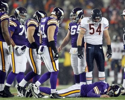 Chicago Bears' Brian Urlacher (54) looks down as Minnesota Vikings quarterback Brett Favre (4) lies on the ground after being hit during the first half an NFL football game Monday, Dec. 20, 2010, in Minneapolis.