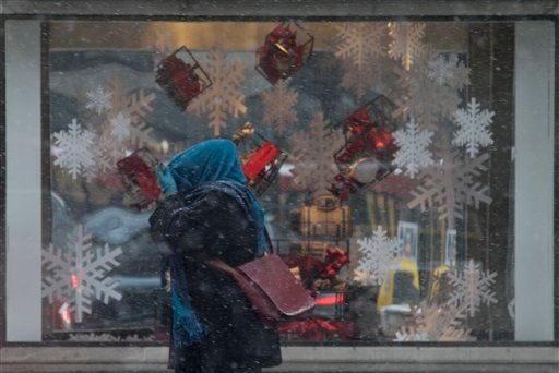 A woman covers her head with her scarf as she walks on the Michigan avenue in the snow in Chicago, Friday, Dec. 24, 2010. (AP Photo/Nam Y. Huh)