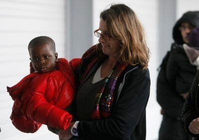 A French adoptive parent carries a Haitian orphan on his arrival in France for adoption by French families, at Roissy airport, outside Paris, Wednesday, Dec. 22, 2010.