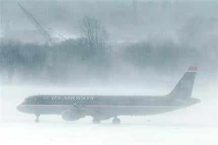 A U.S. Airways jet is seen amidst snow blown by gust of wind at the Philadelphia International Airport in Philadelphia, Monday, Dec. 27, 2010.  (AP Photo/Matt Rourke)