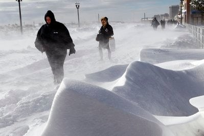 People make their way as heavy winds blow snow across The Boardwalk Monday, Dec. 27, 2010, in Atlantic City, N.J.