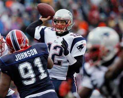 New England Patriots quarterback Tom Brady (12) passes in front of Buffalo Bills defender Spencer Johnson (91) during the first half of an NFL football game in Orchard Park, N.Y., Sunday, Dec. 26, 2010. (AP Photo/Mike Groll)