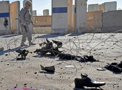 A U.S. army soldier inspects the scene of two suicide bomb attacks in Ramadi, 70 miles (115 kilometers) west of Baghdad, Iraq, Monday, Dec. 27, 2010.