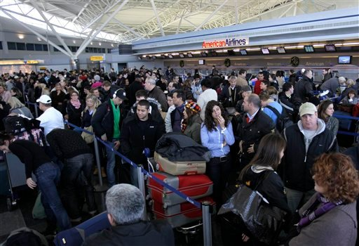 Air travelers wait in line to find out the status of their flights at John F. Kennedy International Airport in New York, Monday, Dec. 27, 2010. (AP Photo/Seth Wenig)