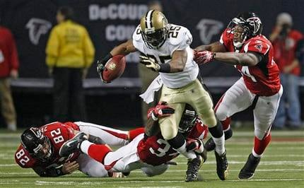 The Atlanta Falcons defense tries to take down New Orleans Saints running back Reggie Bush (25) in the first half of a game at the Georgia Dome in Atlanta on Dec. 27, 2010. (AP Photo/David Goldman)
