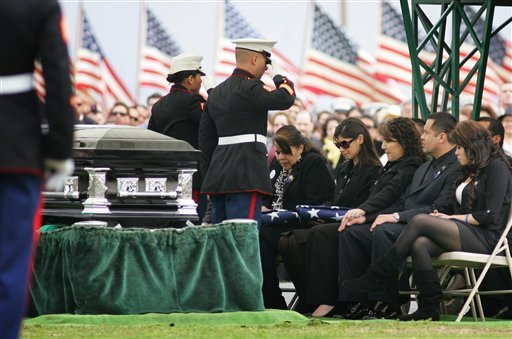 In this March 8, 2010 file photo, Marines salute Saloma Bejar and Mariam Bejar, the mother and wife of fallen officer Javier Bejar, after presenting the ceremonial flag at cemetery services in Reedley, Calif.