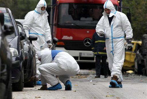 Police forensic experts gather evidence at the scene of a motorcycle bomb that damaged two court administration buildings in Athens, Thursday, Dec. 30, 2010. (AP Photo/Petros Giannakouris)