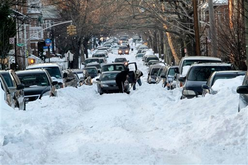 People work to free a car stuck on the unplowed 56th street in the Boro Park neighborhood of the Brooklyn Borough of New York, Wednesday, Dec. 29, 2010. (AP Photo/Mary Altaffer)