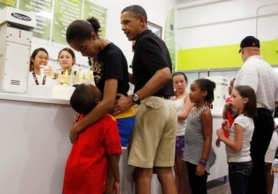 President Barack Obama, third from left, orders shave ice at Island Snow at Kailua Beach Center while on vacation with the first family in Kailua, Hawaii, Monday, Dec. 27, 2010.