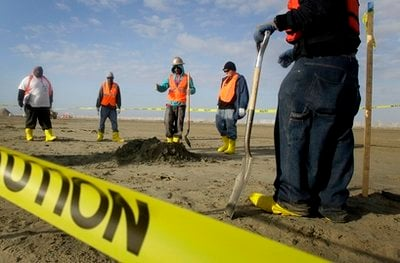 In this Dec. 16, 2010 photo, workers prepare to fill a hole that was dug to search for a layer of tar buried underneath sand on a beach on East Grand Terre Island on the coast of Louisiana.