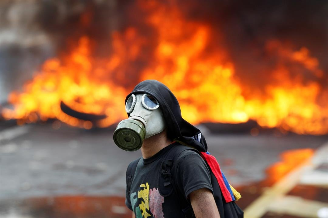 An anti-government protester stands in front of burning barricade on a highway in Caracas, Venezuela, Monday, April 24, 2017. (AP Photo/Ariana Cubillos)
