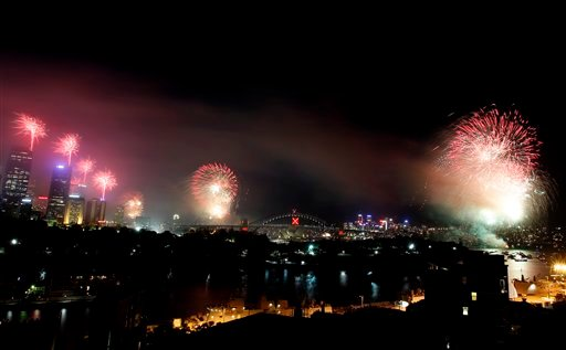 The sky above Sydney Harbour lights up with the 9 p.m. fireworks display on new year's eve in Sydney, Australia, Friday, Dec. 31, 2010. (AP Photo/Rob Griffith)