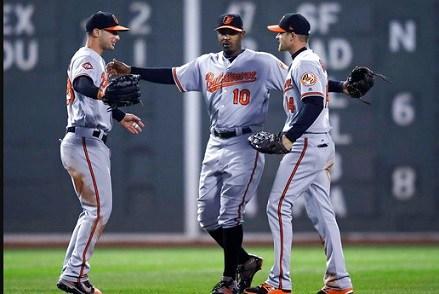 Baltimore Orioles center fielder Adam Jones (10) celebrates with right fielder Craig Gentry, right, and left fielder Joey Rickard left.