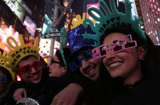 A group of friends pose for photographs as they take part in the New Year's Eve festivities in New York's Times Square Friday Dec. 31, 2010. (AP Photo/Tina Fineberg)