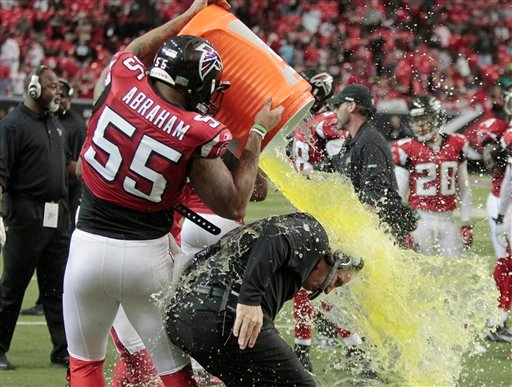 Atlanta defensive end John Abraham (55) dumps a cooler of liquid on Atlanta Falcons head coach Mike Smith in the final seconds of their 31-10 victory over Carolina Panthers in an NFL football game Sunday, Jan. 2, 2011 in Atlanta. (AP Photo/John Bazemore)