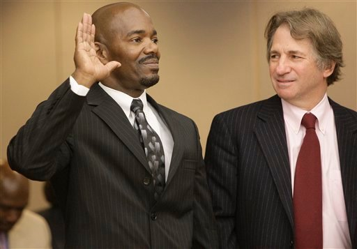 Cornelius Dupree Jr., left, raises his hand to testify while attorney Barry Scheck, right, looks on in Dallas on Tuesday, Jan. 4, 2010. Dupree served 30 years for rape and robbery before being exonerated by DNA evidence. (AP Photo/Mike Fuentes)