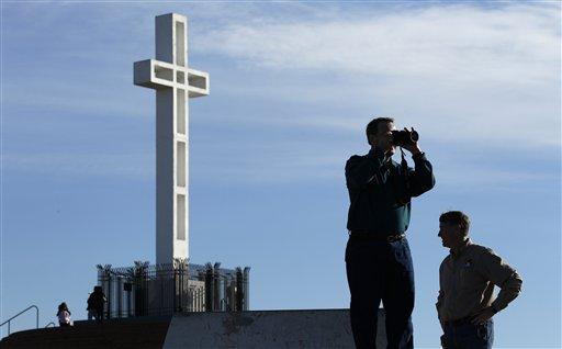 Rev. John Fredericksen of Orlando, Fla., takes a picture in front of the war memorial cross on Mount Soledad Tuesday, Jan. 4, 2011, in San Diego, alongside Burdette Streeter of San Diego.