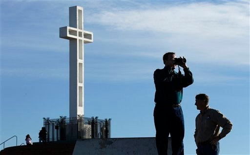 Rev. John Fredericksen of Orlando, Fla., takes a picture in front of the war memorial cross on Mount Soledad Tuesday, Jan. 4, 2011, in San Diego, alongside Burdette Streeter of San Diego.