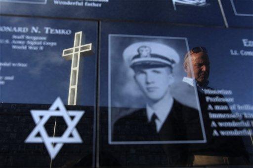 A man looks at plaques honoring soldiers below a war memorial cross on Mount Soledad.