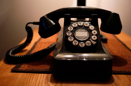 In this Wednesday, April 14, 2016 photo, a push-button landline telephone is seen in Whitefield, Maine. Across the country, telecom companies are lobbying lawmakers to be released from their mandate of providing service to every home. (AP Photo/Robert F.