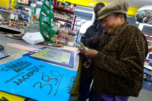 Loretta Pride, right, smiles after receiving help from Ivey Coples with selecting numbers for her three Mega Millions lottery tickets at the The All In One Shop, Jan. 4, 2011, in Greensboro, N.C. (AP Photo/News & Record, Jerry Wolford)