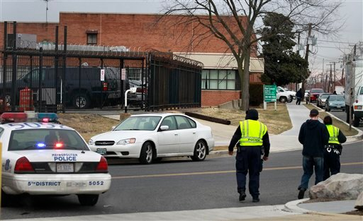 Law enforcement officials are seen near a postal sorting facility in Washington, Friday, Jan. 7, 2011, after a package ignited.